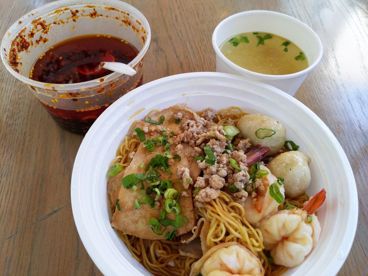 A bowl of noodle soup with shrimp, pork, and fish balls, with broth and chile oil in separate bowls, above.