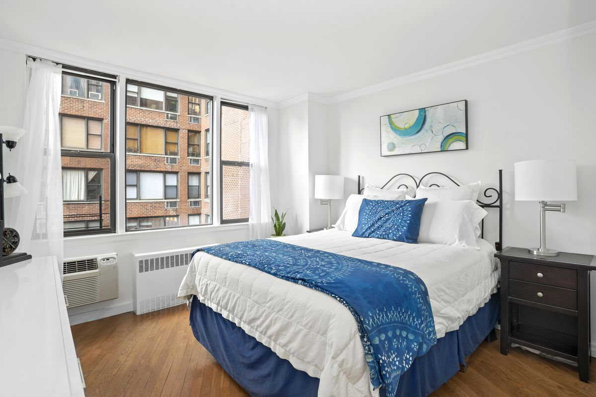 A bedroom with a large bed, a large window, and hardwood floors.