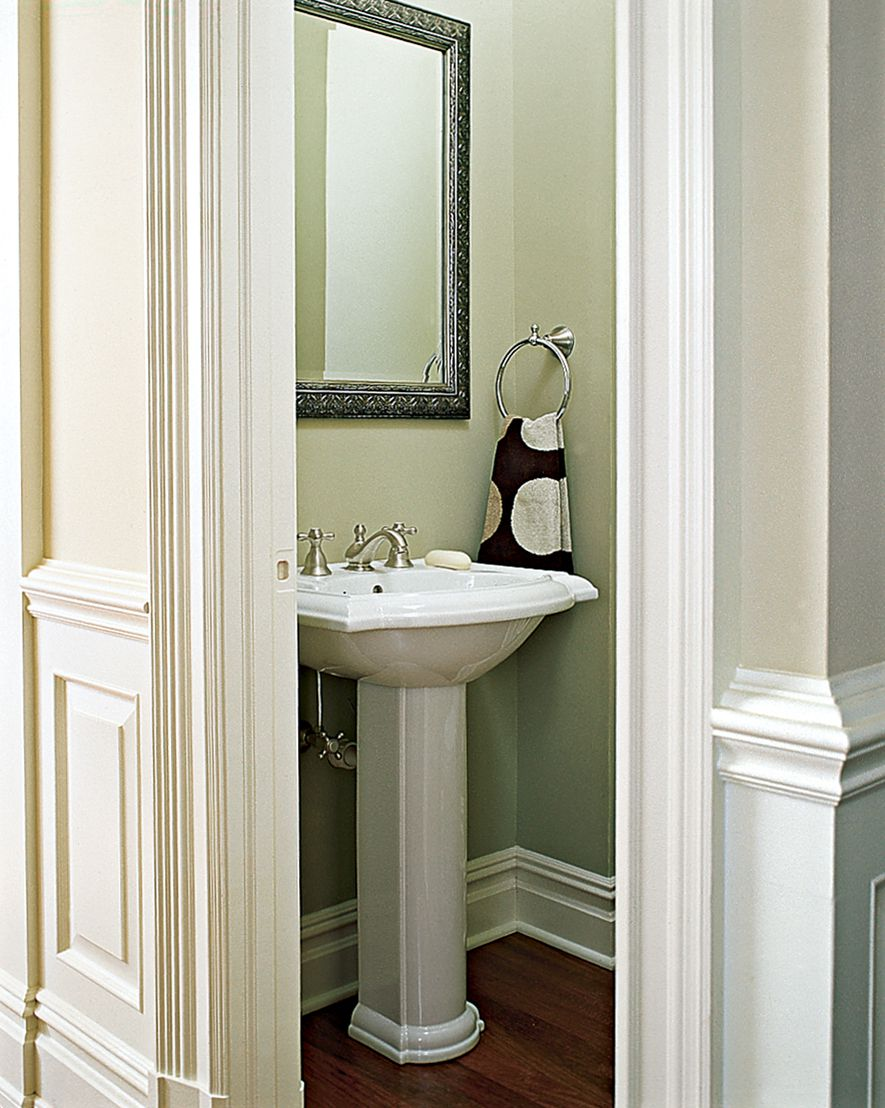 <p><strong>Cozy Classic</strong><br> A petite Kohler pedestal sink keeps a snug 4-by-5-foot space designed by Steven Lecher from seeming cramped. The edges of the basin and pedestal base echo the moldings in and around the half bath.</p>