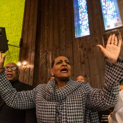 Radio host Pam Morris-Walton raises her arms and sings while a gospel hymn is sung by the church choir, during the wake and funeral.