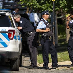 Chicago police personnel investigate after an officer shot an alleged suspect inside an apartment in the 6200 block of West Grand Avenue, Monday morning, July 8, 2019.