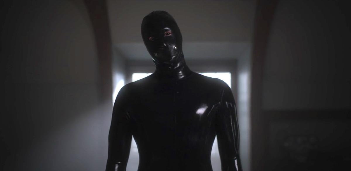 a figure in a black rubber suit
