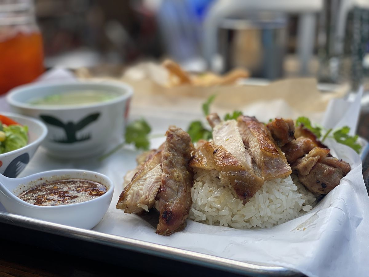 Lemongrass grilled chicken sits over ginger rice on a paper-lined metal tray; a cup of chicken soup sits in the background