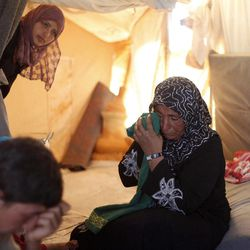 In this Tuesday, Sept. 11, 2012 photo, the 46-year-old wife of farmer Ghassan Baradan, who fled her southern restive border town of Daraa, Syria with her family in July, wipes her eyes as she speaks during an interview at the Zaatari Refugee Camp, in Mafraq, Jordan. Jordan now hosts 200,000 Syrians, the largest number of refugees of any neighboring country. After months of delay, Jordan finally opened its first official refugee camp in July at Zaatari, near the border with Syria.