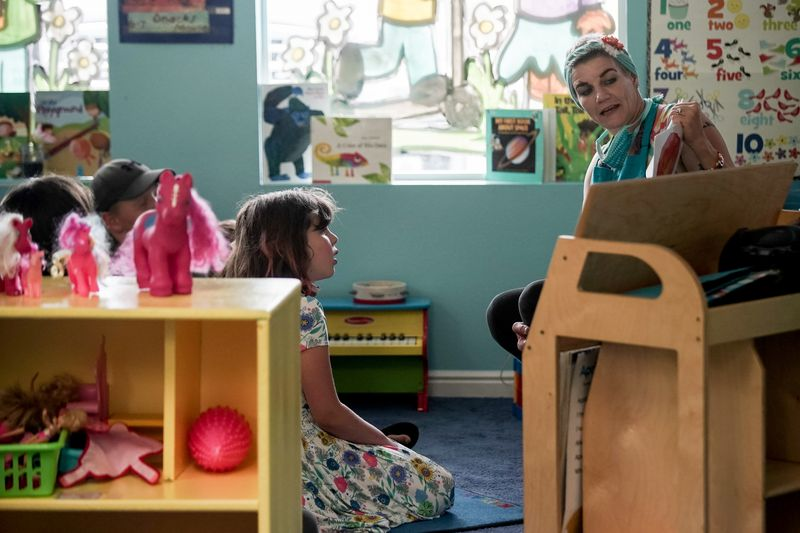 Preschool teacher DiVina Warren reads to Lilly Virga, 7, center, and other children at Sunshine Academy Preschool & Daycare in Alpine on Thursday, May 14, 2020. Sunshine Academy is one of several child care centers that have been approved to reopen, with a number of strict new operating guidelines, to serve the children of essential workers during the COVID-19 pandemic.