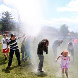 Students run through a water cannon to celebrate the last day of school at Crestview Elementary in Holladay on Friday, May 27, 2016.