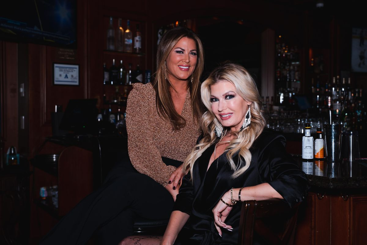 One woman stands and another sits at a bar