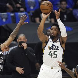 Utah Jazz guard Donovan Mitchell, right, shoots as Los Angeles Clippers guard Terance Mann defends during the first half in Game 6 of a second-round NBA basketball playoff series Friday, June 18, 2021, in Los Angeles.