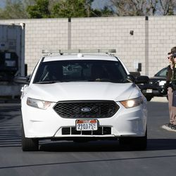 Law enforcement officers salute as an Ogden police car leaves the Utah Medical Examiner's Office in Taylorsville on Thursday, May 28, 2020. Police said one Ogden officer and a suspect were killed, while another officer was injured, in an exchange of gunfire earlier in the day.