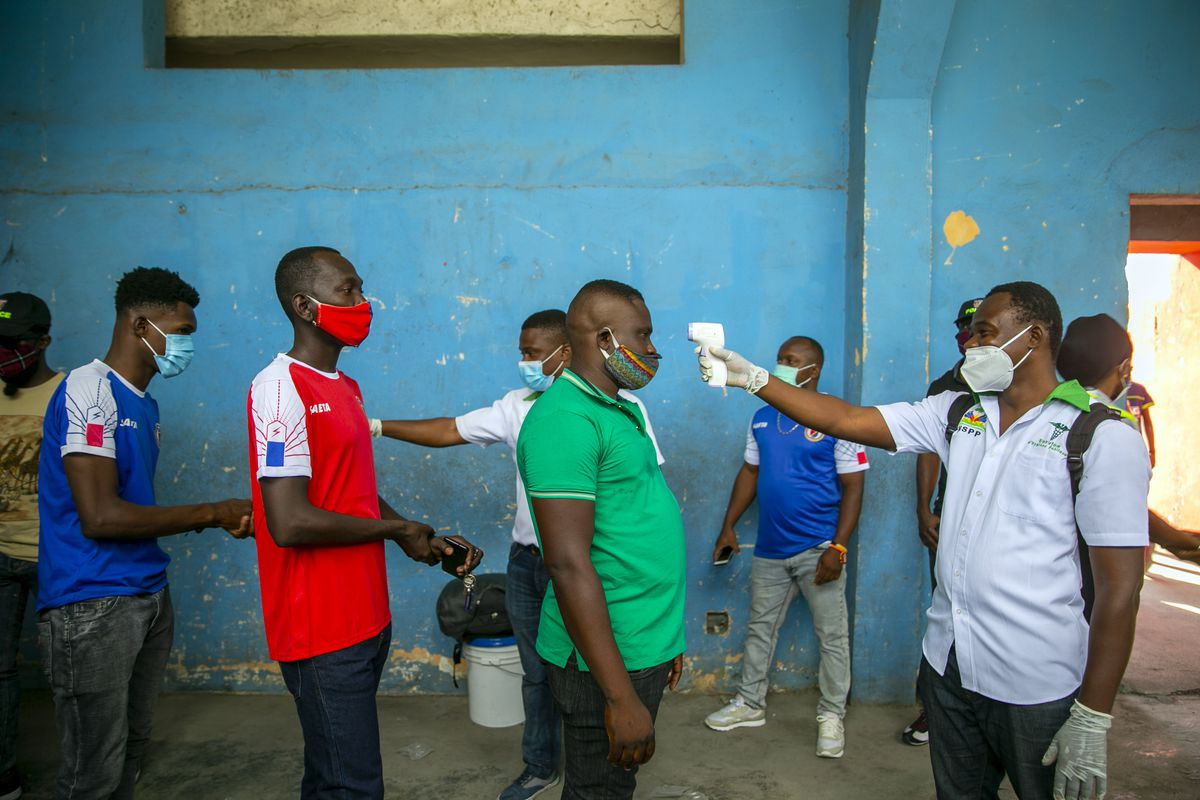 Health ministry workers check the temperature of mask-wearing fans as a precaution against the spread of the new coronavirus, before entering the stadium prior to the start of the CONCACAF World Cup qualifying soccer match between Haiti and Belize in Port-au-prince, Haiti, Thursday, March 25, 2021.