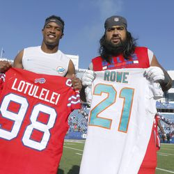Miami Dolphins cornerback Eric Rowe, left, and Buffalo Bills defensive tackle Star Lotulelei, right, pose at midfield after swapping jerseys following an NFL football game, Sunday, Oct. 20, 2019, in Orchard Park, N.Y.