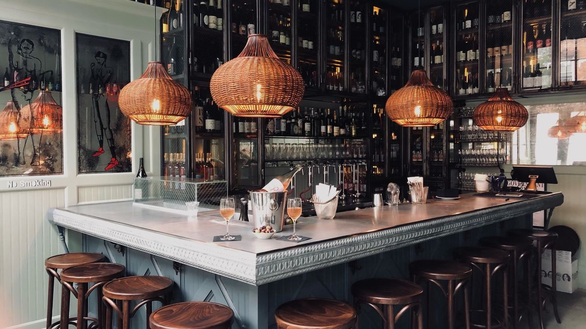 An L-shaped bar counter with multiple dark wooden stools pulled up and custom light fixtures hanging overhead