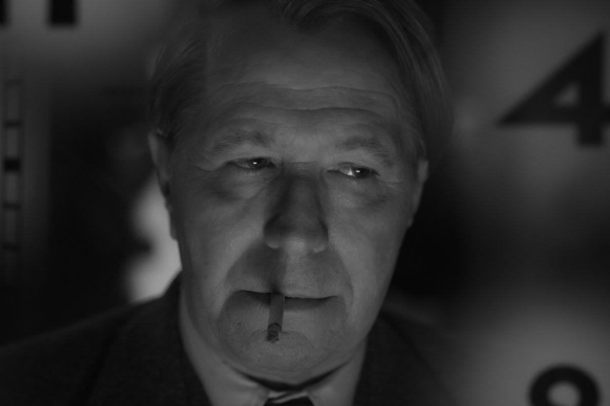 A man smokes a cigarette in black and white.