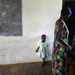 """In this photo taken Friday, April 27, 2012, Adye Sunday, 25, right, who was abducted when she was 13 by Lord's Resistance Army (LRA) leader Joseph Kony and forced to be one of his dozens of """"wives"""" and says he's also the father of her two children, one of whom Betty, 3, stands at left, prepares food to sell at a center set up to help those who have left or fled the LRA, in Gulu, Uganda. Adye Sunday isn't sure about the calls to kill or capture LRA leader Joseph Kony, who inspires conflicted thoughts among some people in northern Uganda, despite more than 3,000 children being abducted by the LRA since 2008, according to the U.N. and Human Rights Watch. (AP Photo/Ben Curtis)"""