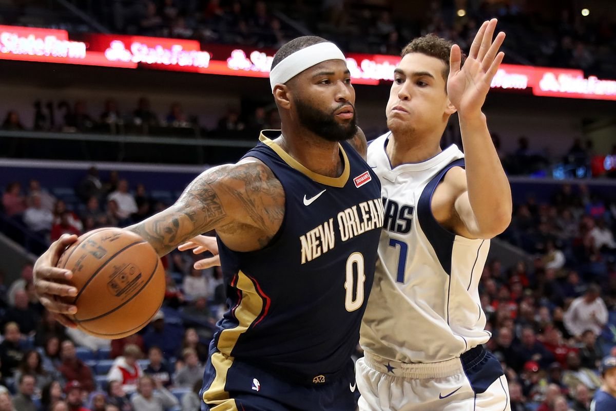 DeMarcus Cousins passes the ball around Dwight Powell