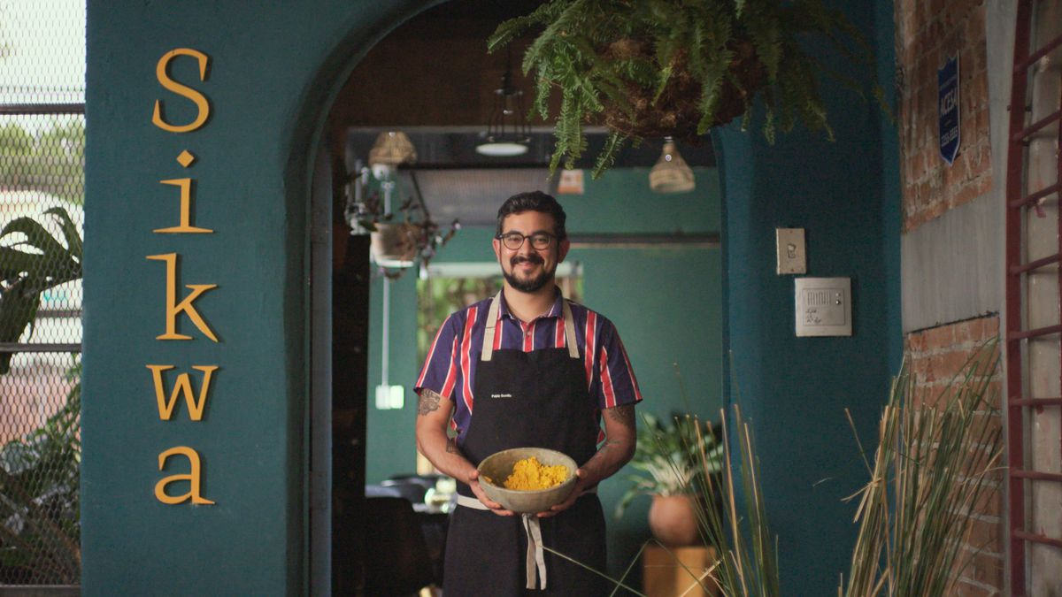 A chef stands in front of a restaurant holding a bowl.