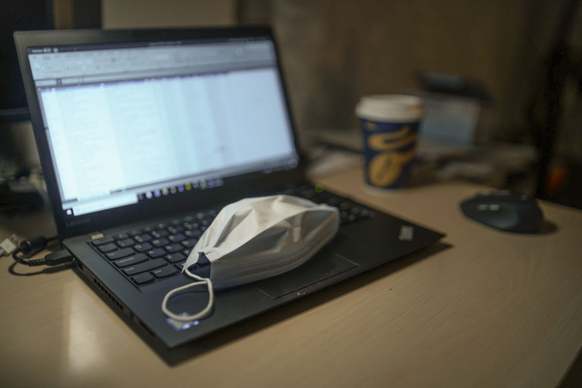 A protective face mask resting on the keyboard of a laptop computer.