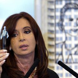 Argentina's President Cristina Fernandez holds up a tube with a sample of the first oil extracted in the country, during her announcement of a bill to nationalize Spain's controlled oil company YPF, at Government House in Buenos Aires, Argentina, Monday April 16, 2012. Fernandez said in an address to the country that the measure sent to congress on Monday is aimed at recovering the nation's sovereignty over its hydrocarbon resources. Behind Fernandez is a scale model of an iron sculpture of Argentina's former first lady and second wife of late President Juan Peron, Eva Peron.