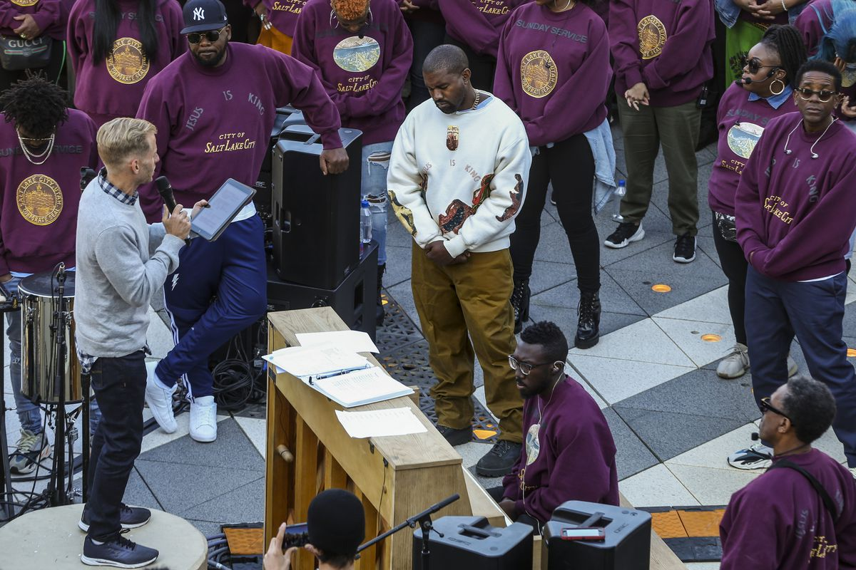 """Kanye West, white sweater, bows his head in prayer during his """"Sunday Service"""" at The Gateway in Salt Lake City on Saturday, Oct. 5, 2019. Thousands packed into the outdoor mall, causing people to stand on and climb up anything they could find to catch a glimpse of West."""