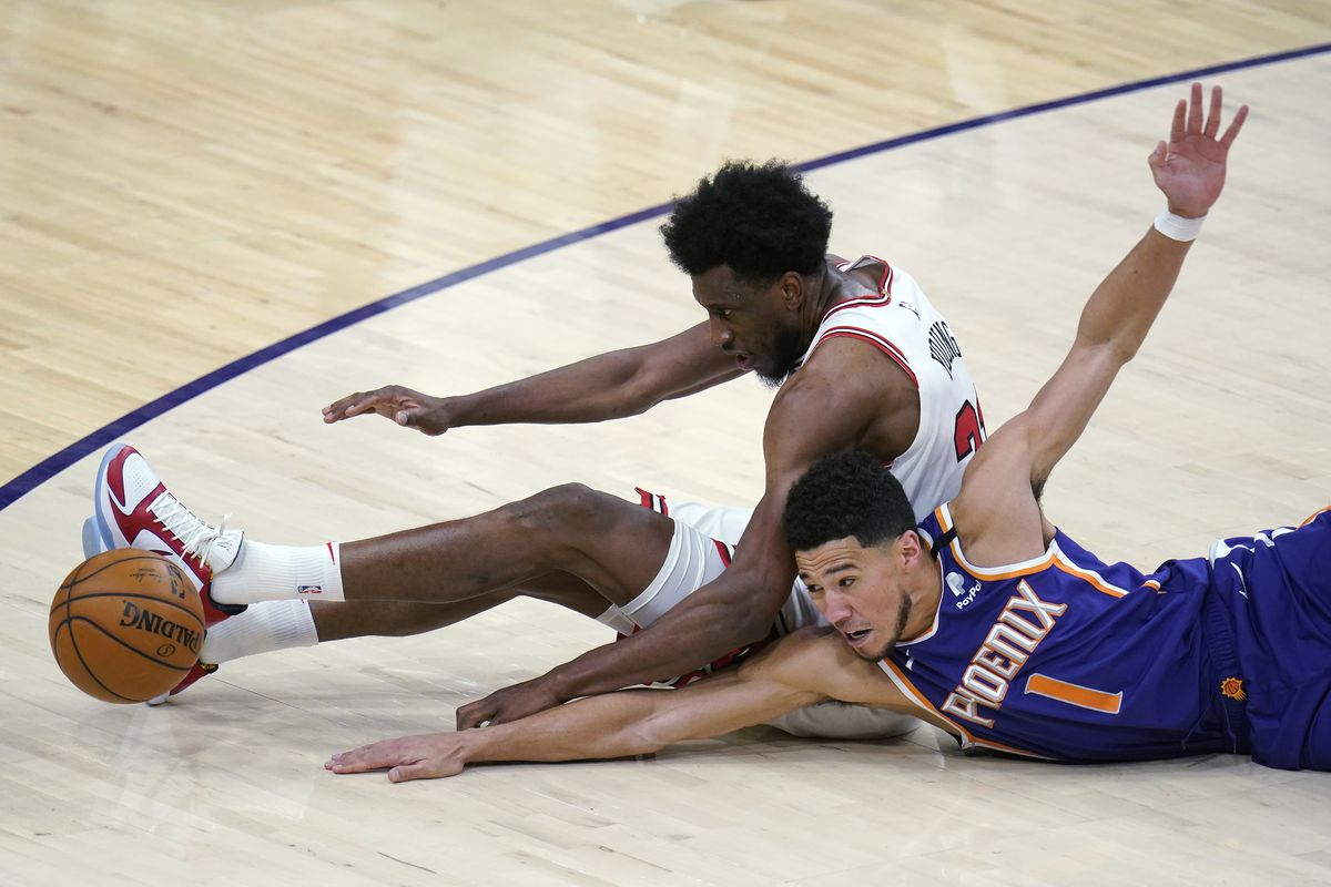 Suns guard Devin Booker and Bulls forward Thaddeus Young scramble for the ball during Wednesday's game.