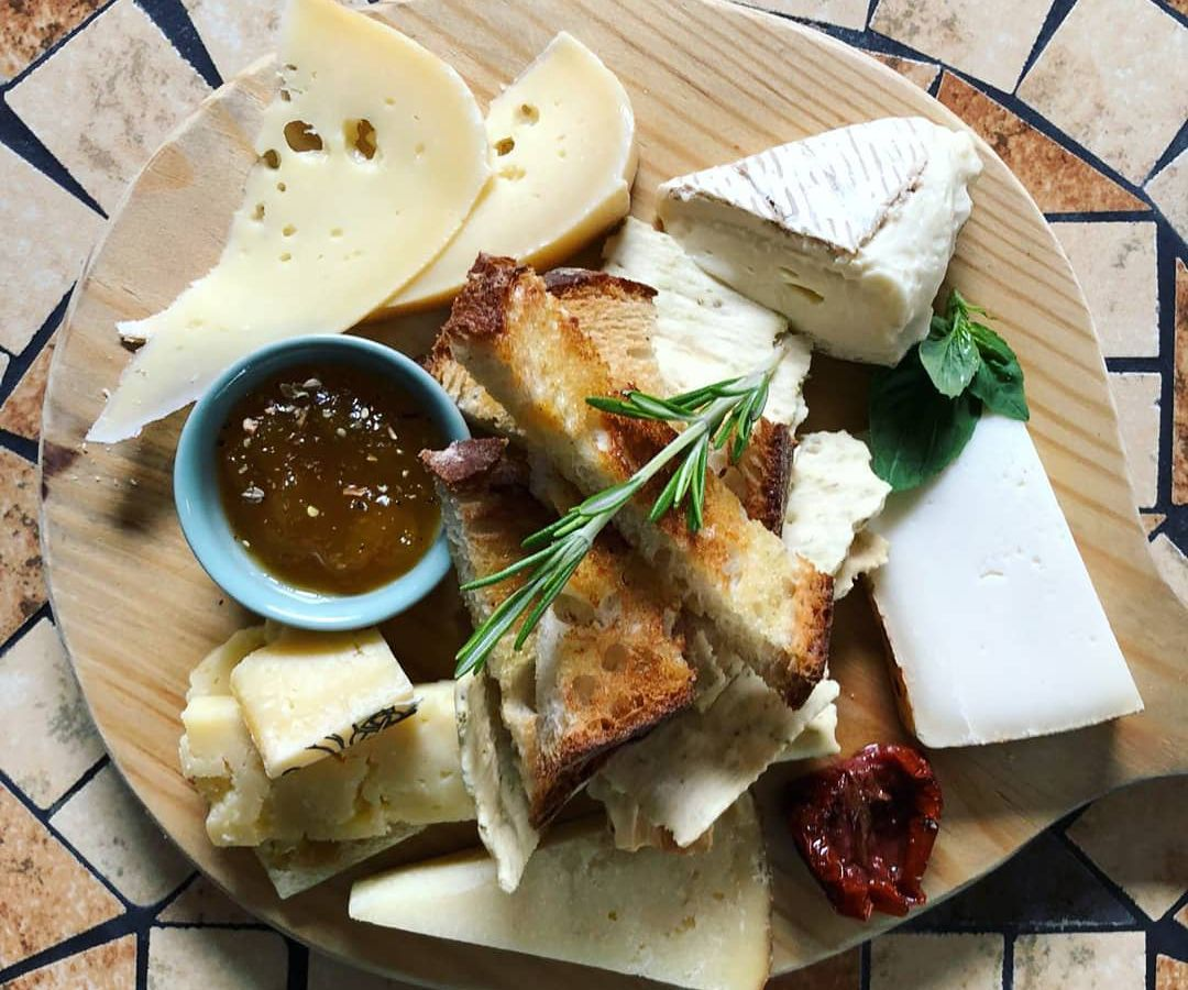 From above, a cheese board with various cheeses both hard and soft, slices of toast, a small cup of jam, and a sprig of tarragon on top, sitting on a patterned tile floor