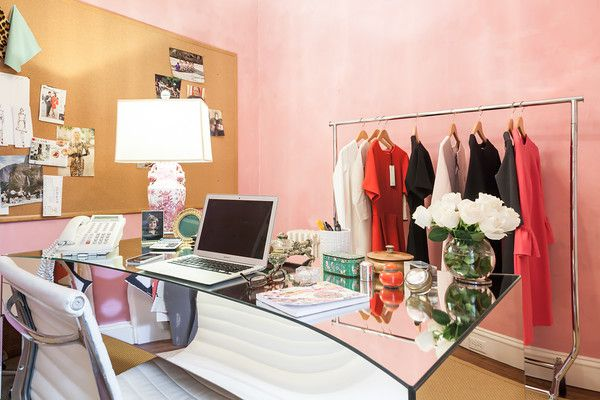 A room with a desk, chairs, bulletin board, and a rolling rack with clothing. The walls are pink.