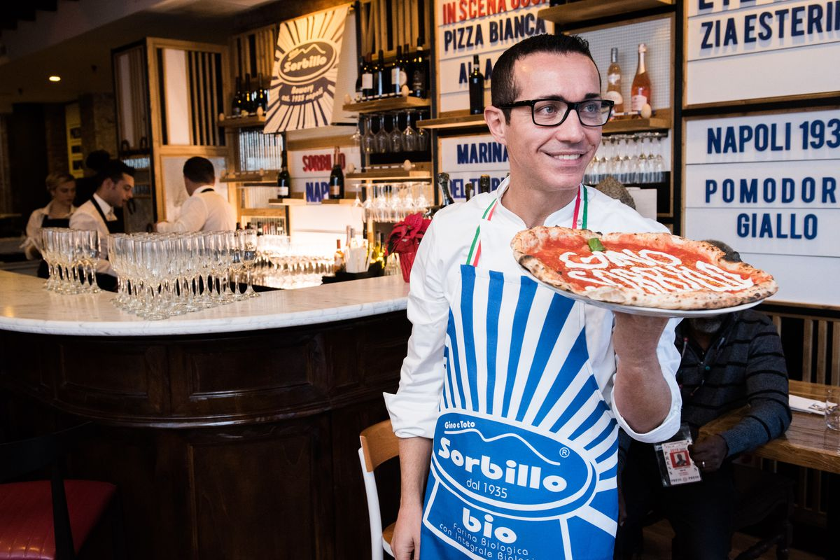 Neapolitan pizza maestro Gino Sorbillo at his Miami pizzeria, with a pizza with his name on it