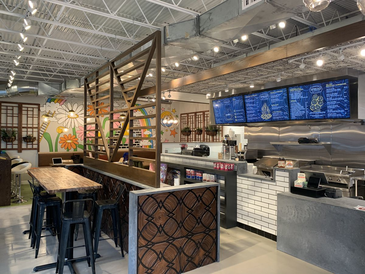 bagel shop with counter, booths, and flower mural