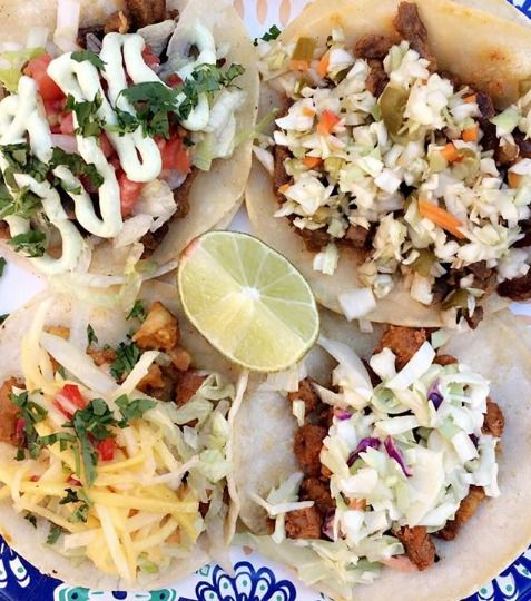 A selection of meat-filled tacos drizzled with sauce and toppings, alongside a slice of lime