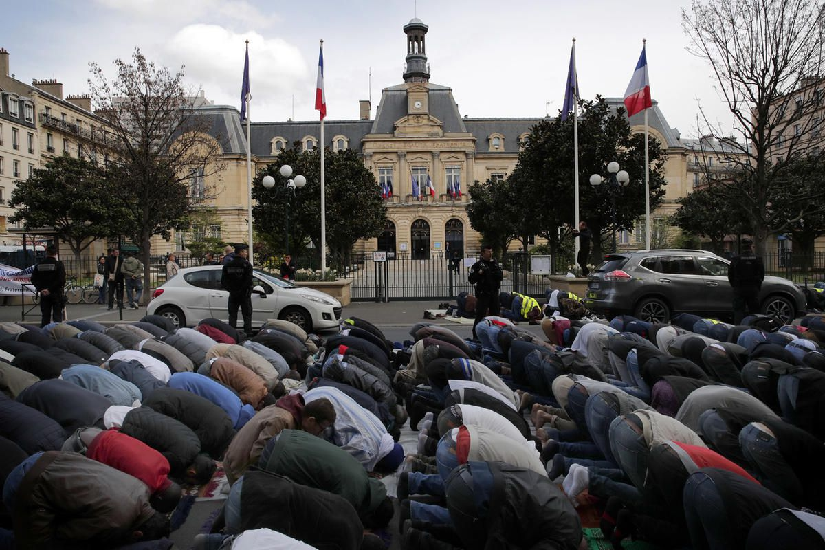 Hundreds of Muslims pray on the street in front of the town hall plaza, seen behind, in the Paris suburb of Clichy la Garenne, Friday, March 31, 2017. They protest the closure of a prayer room and call attention to their wishes for a mosque in their town,