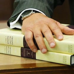 LDS Church Historian and Recorder Elder Steven E. Snow, rests his hand on a pair of the new volumes as the LDS Church, in cooperation with the Community of Christ announces the release of the printers manuscript of the the Book of Mormon, during a press conference Tuesday, Aug. 4, 2015, at the LDS Church's History library in Salt Lake City.