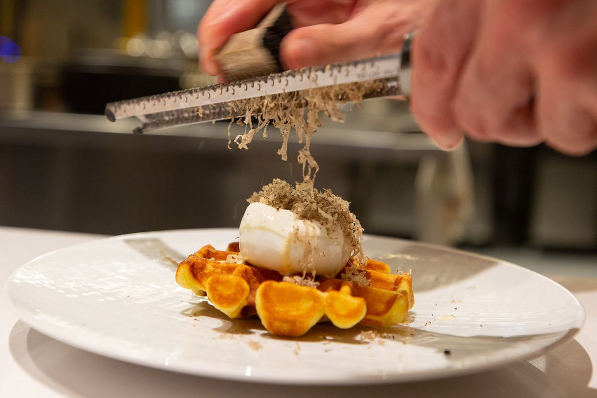 A hand shaving truffle over a dish at Bisato in Pioneer Square.