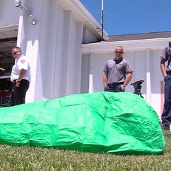 A Sandy firefighter practices getting into an emergency fire shelter Monday, July 1, 2013, while others look on. Once inside the sleeping-bag type cover, the firefighter gets as close to the ground as possible and waits for word to get out. Shelters are made of reflective material and can only be used once. The green shelter is used during practice.