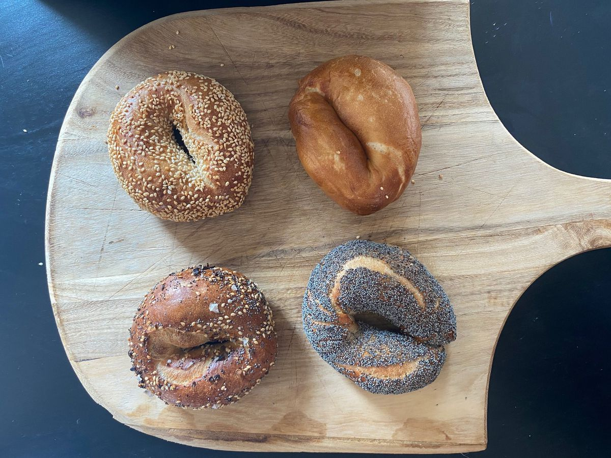 four bagels on a wooden pizza board