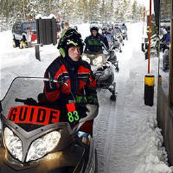 A guide prepares to lead a group of snowmobilers inside Yellowstone National Park in Montana. A federal judge on Friday struck down the Clinton-era ban on snowmobiles in Yellowstone and Grand Teton national parks.