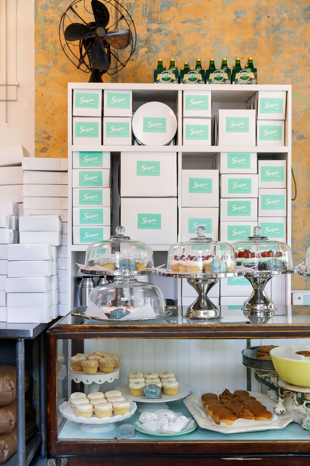 The interior of a bakery. In the foreground is a glass bakery case with cakes and baked goods on display. In the background is a shelving unit with many bakery boxes stacked. An electric fan sits on top of the shelving unit.
