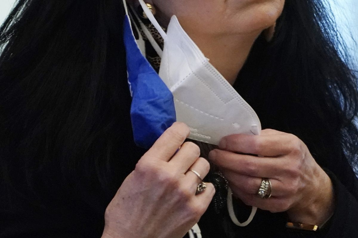 In this Thursday, Feb. 4, 2021, file photo, a state legislator adjusts her face masks while asking a question at the Capitol in Jackson, Miss. States across the U.S. are changing their mask mandates. This will be a running list of changes to mandates and orders.