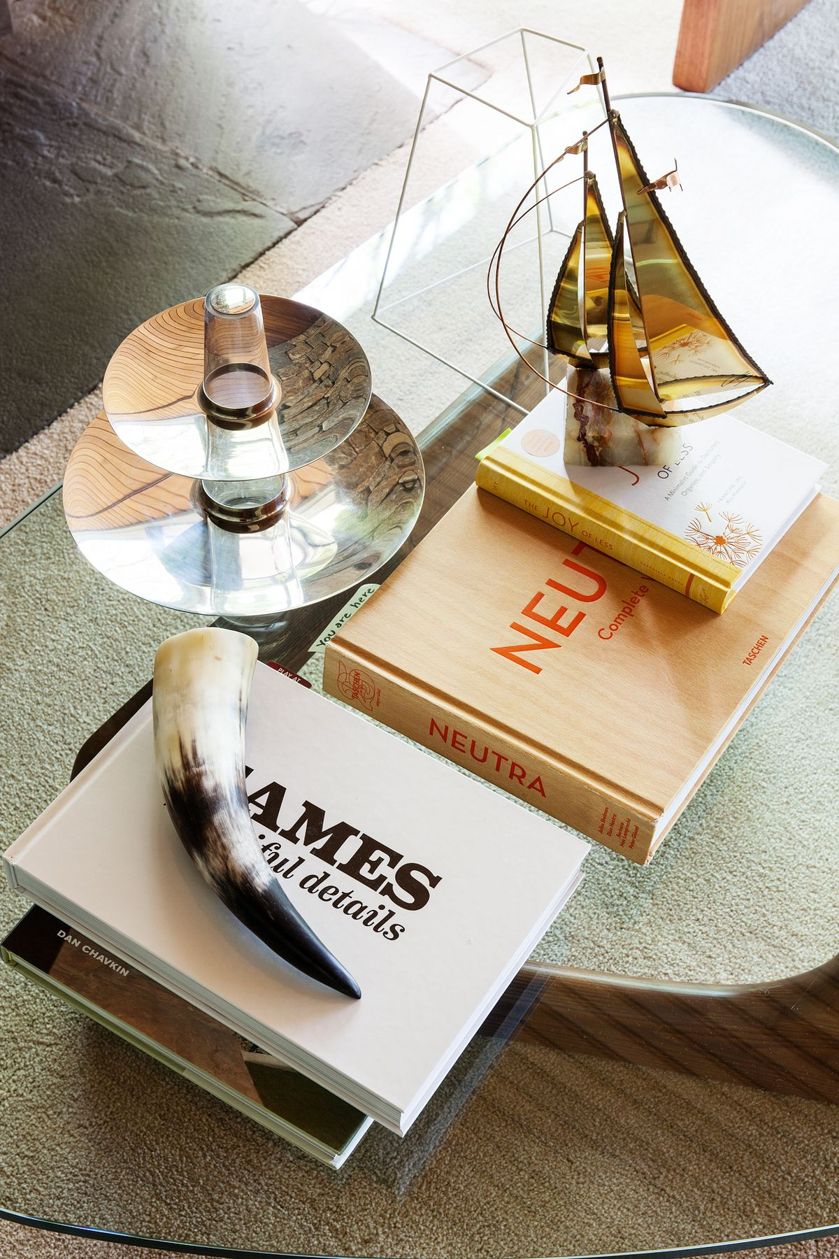 A coffee table vignette shows midcentury accessories, a metal boat and tiered tray, as well as books about Neutra and Eames.