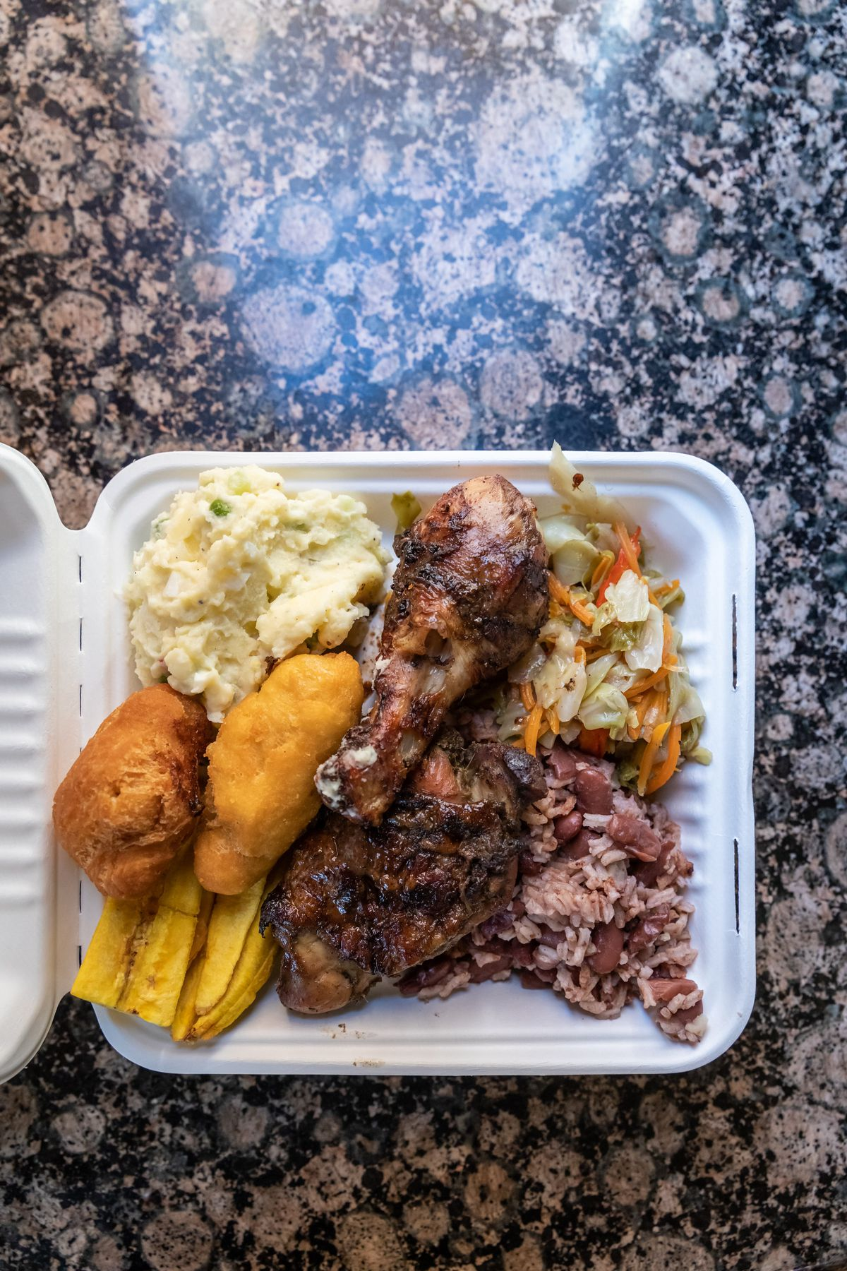 Plate of jerk chicken, red beans, and rice, and more at Jerky Jerk in a paper takeout tray.