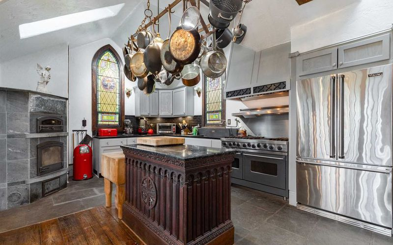 A kitchen has a large rustic looking island, shiny stainless steel appliances, and stained glass windows.