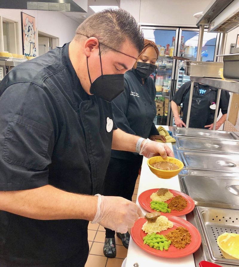 Chef Adrian Arias adds gravy to a plate of pureed food that has been formed into its original shape to make it more appealing to residents who have trouble swallowing due to dementia at Northbrook Inn Memory Care Community. Fellow chef Keyva Linton looks on.