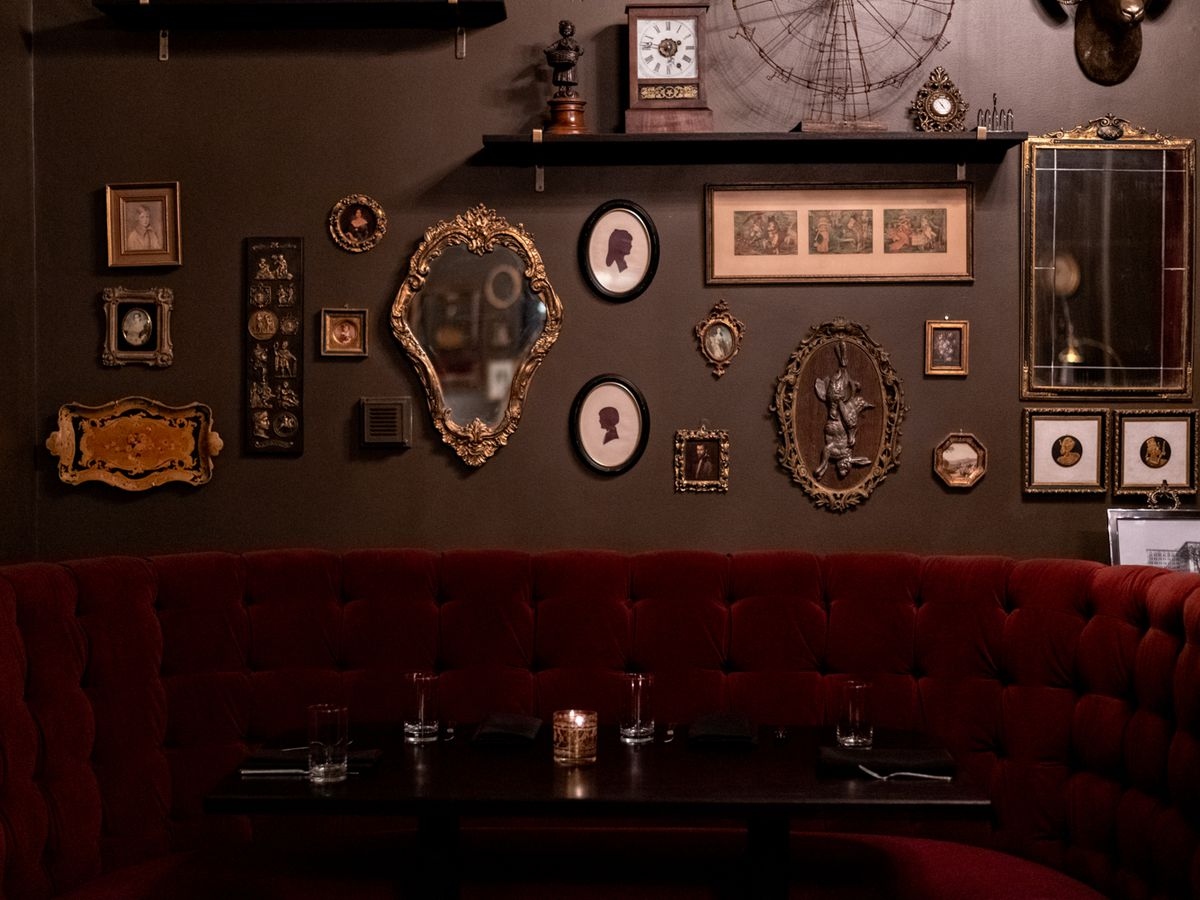 The dark dining room with plenty of small, Victorian style pictures