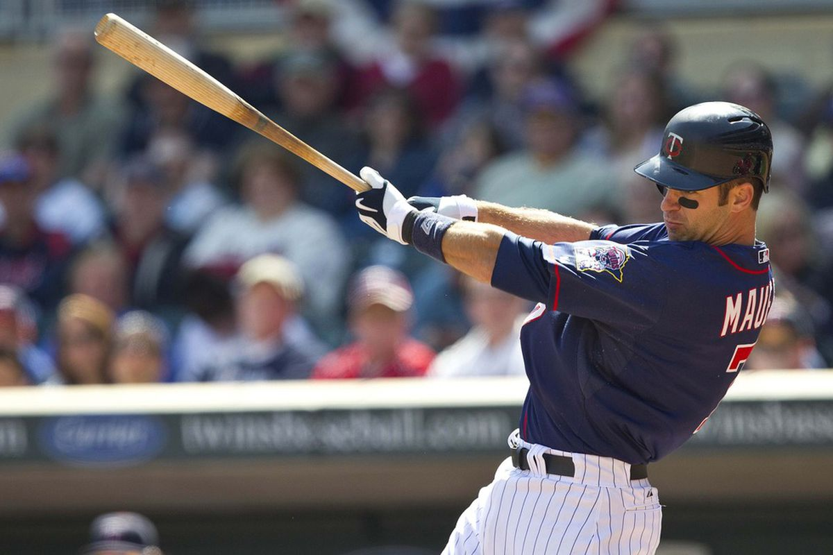 Apr 12, 2012; Minneapolis, MN, USA: Minnesota Twins catcher Joe Mauer (7) hits an infield single in the sixth inning against the Los Angeles Angels at Target Field. The Twins won 10-9. Mandatory Credit: Jesse Johnson-US PRESSWIRE