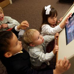 Josiah Kleven, top left, Hyrum Torres, bottom left, Ezra Kleven, center, and Sophia Torres investigate a touch screen display at the North Visitors' Center during the Saturday afternoon session of the 176th Annual General Conference for The Church of Jesus Christ of Latter-day Saints at the Conference Center in Salt Lake City Saturday, April 1, 2006.
