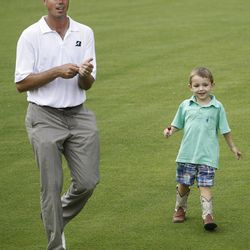 Matt Kuchar walks up the 18th fairway with his son, Cameron, during a weather delay in the final round of the Memorial golf tournament at Muirfield Village Golf Club in Dublin, Ohio Sunday, June 5, 2011.