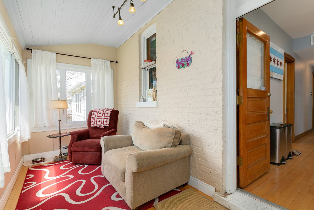 Sunroom with a painted brick wall and line of windows with white curtains. There are two plush chairs.