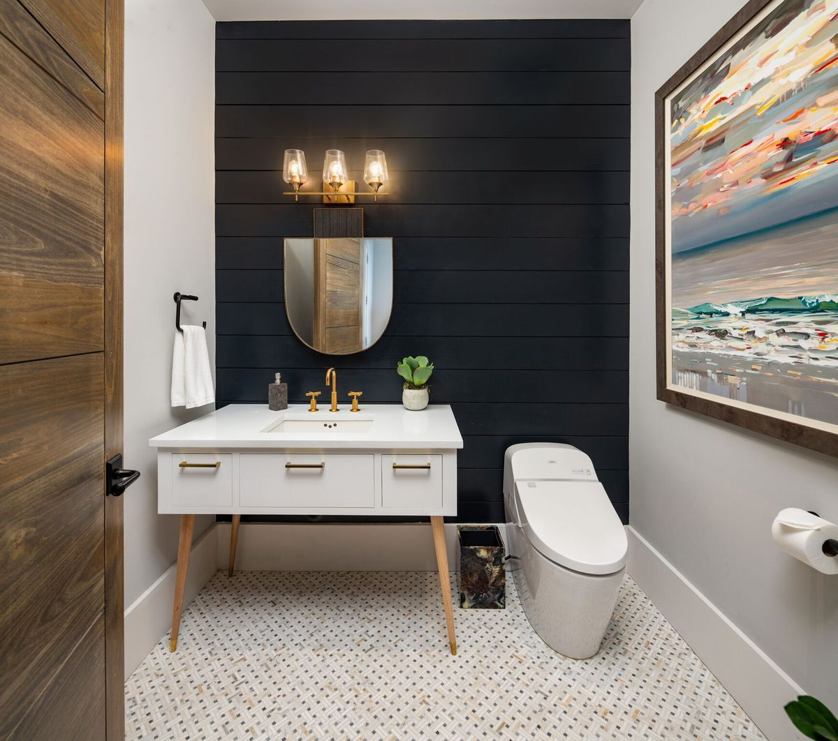 A bathroom with blue shiplap walls and a great art piece at right.