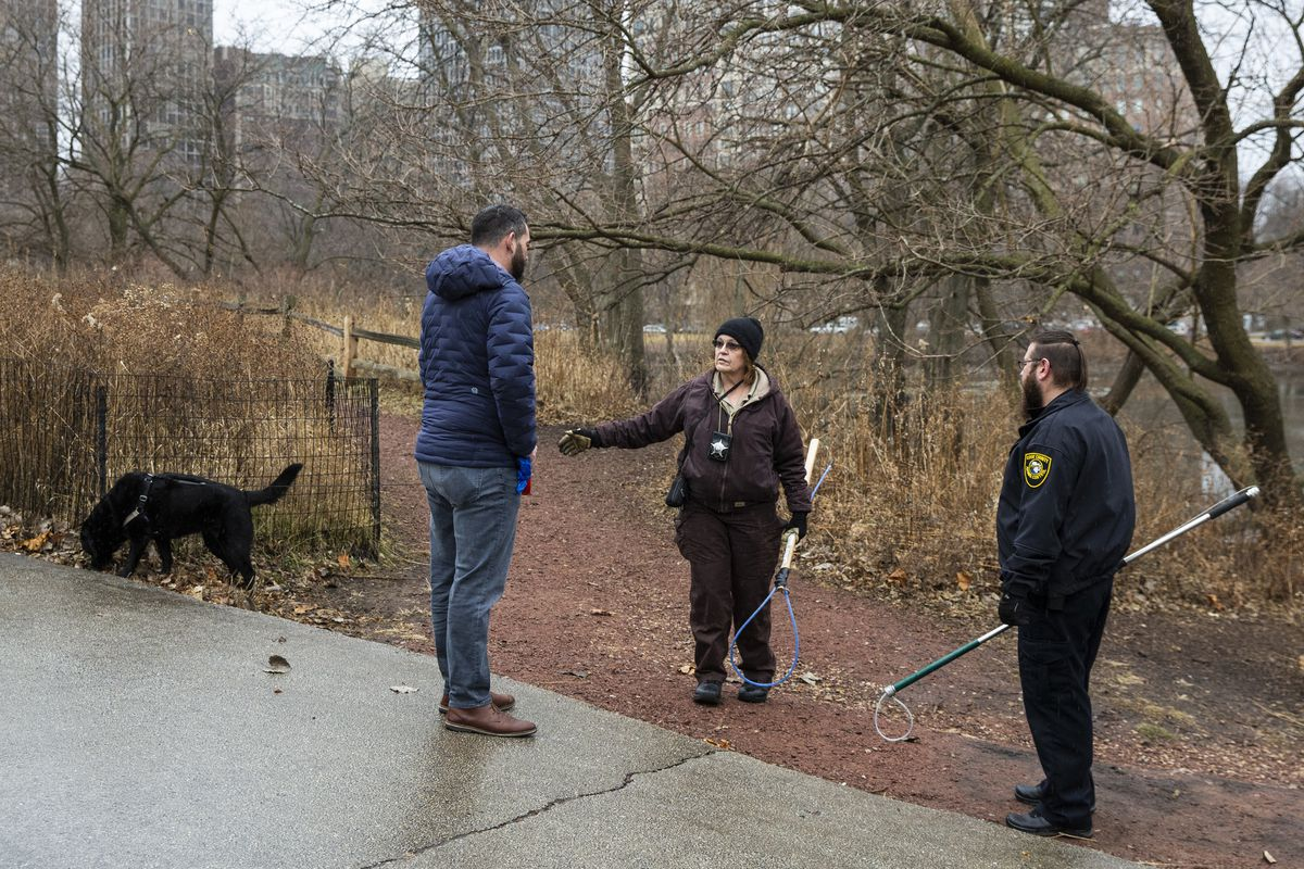 An inspector from Chicago Animal Care and Control and warden from Cook County Animal Control take a break from searching for a coyote den to chat with a man walking a dog near the Peggy Notebaert Nature Museum in Lincoln Park, Thursday morning, Jan. 9, 2020. Two people — including a 6-year-old boy bit multiple times near the museum — were attacked by a coyote in separate incidents Wednesday in Chicago.