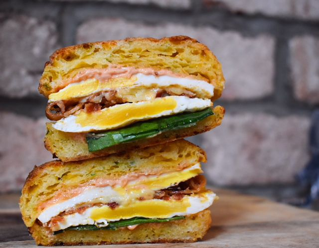 Two halves of a breakfast sandwich stacked high on top of each other. Egg, meat, and greens are visible.