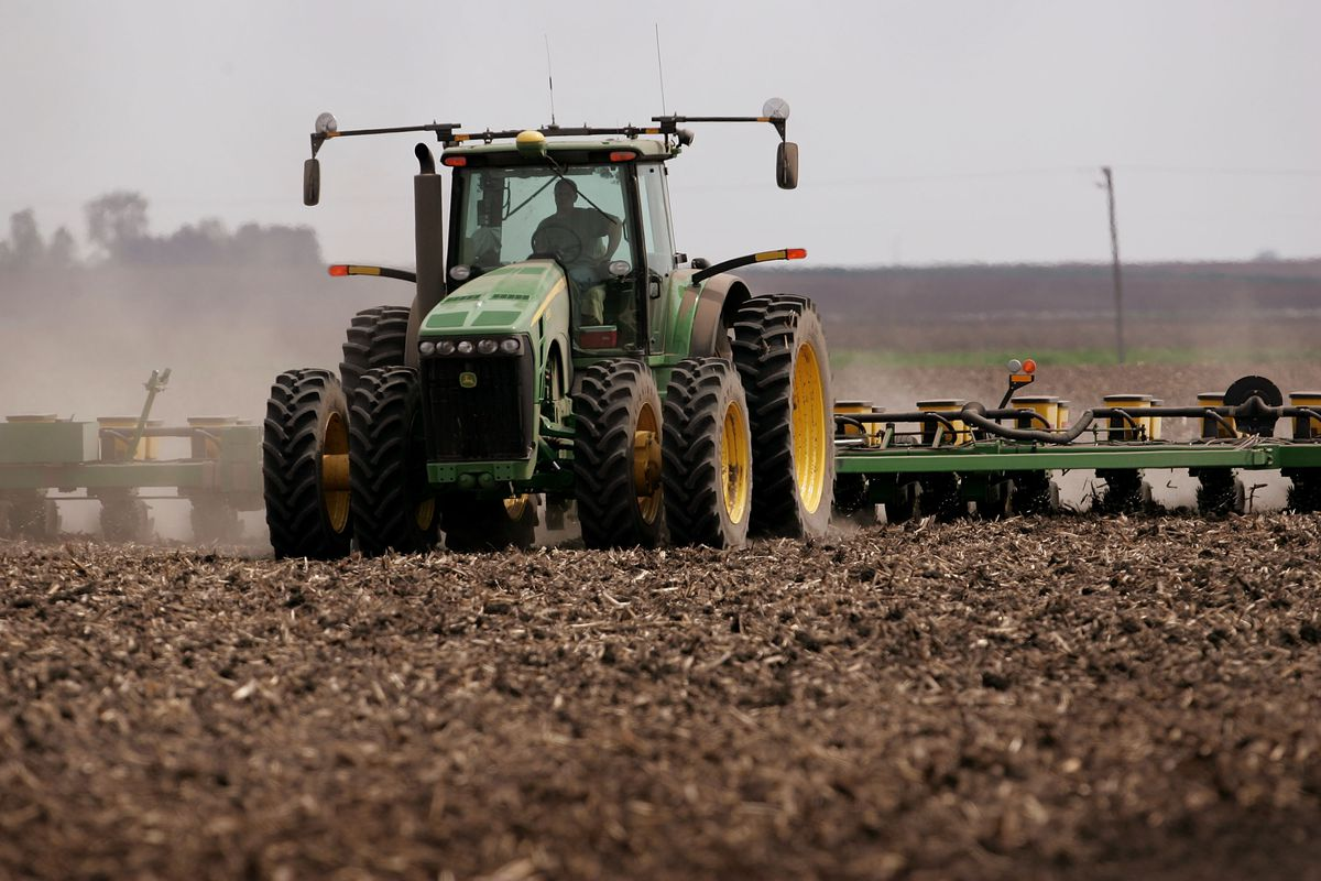 Farmer Brent Carmichael plants corn with his tractor in a field he farms with his father May 8, 2007 near Rochelle, Illinois.